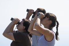 Tres personas están mirando los prismáticos grandes El Birdwatching y concepto del espía imágenes de archivo libres de regalías