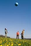 Tres personas jovenes con la bola Imágenes de archivo libres de regalías