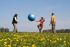 Tres personas jovenes con la bola Fotos de archivo libres de regalías