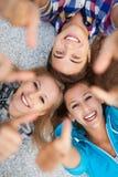 Tres personas jovenes con los pulgares para arriba Imágenes de archivo libres de regalías