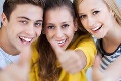 Tres personas jovenes con los pulgares para arriba Imagen de archivo libre de regalías