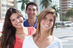Tres personas jovenes de risa en la ciudad Imagen de archivo