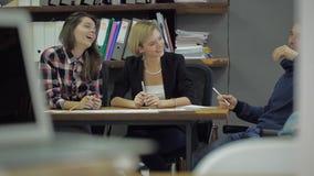 Tres personas jovenes que ríen y que discuten algo que se sienta en un escritorio en la oficina almacen de metraje de vídeo