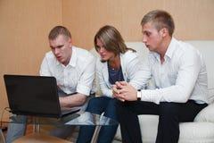 Tres personas jovenes que se sientan en el sofá con PC Imagen de archivo