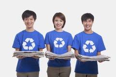 Tres personas jovenes sonrientes que colocan en fila los periódicos que llevan y que llevan reciclando las camisetas del símbolo,  Imagenes de archivo