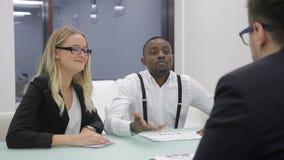 Tres personas multi-étnicas están teniendo negociaciones de un negocio en oficina moderna almacen de video