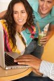 Tres personas que cenan hacia fuera usando una computadora portátil Imágenes de archivo libres de regalías