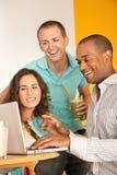 Tres personas que cenan hacia fuera usando una computadora portátil Imagen de archivo libre de regalías