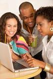 Tres personas que cenan hacia fuera usando una computadora portátil Fotografía de archivo libre de regalías