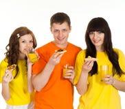 Tres personas que comen la pizza Imagen de archivo