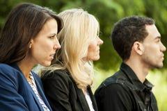 Tres personas que miran a la derecha. Fotografía de archivo