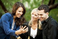 Tres personas que miran un teléfono Fotos de archivo libres de regalías