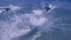 Tres personas que practica surf atléticas que se zambullen en el mar almacen de video