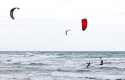 Tres personas que practica surf de la cometa Fotografía de archivo