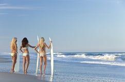 Tres personas que practica surf de las mujeres con las tablas hawaianas en la playa Imágenes de archivo libres de regalías