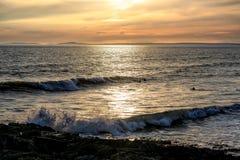 Tres personas que practica surf y una puesta del sol foto de archivo libre de regalías