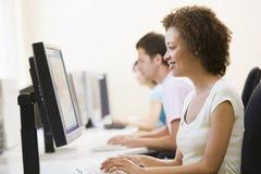 Tres personas que se sientan en pulsar de la sala de ordenadores Fotografía de archivo libre de regalías