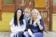 Tres personas se están sentando en el pórtico de madera Fotos de archivo
