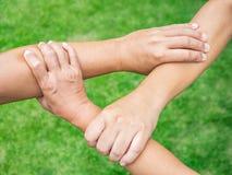 Tres personas se unen a las manos juntas en fondo de la hierba Amistad imagen de archivo