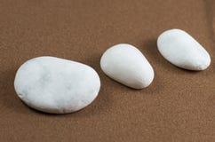 Tres piedras blancas en la arena de Brown Imagenes de archivo