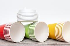 Tres pilas de amarillo, de rojo y de verde se llevan las tazas de papel disponibles con los casquillos que mienten en el escritor imagen de archivo libre de regalías
