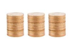 Tres pilas de monedas de oro Imágenes de archivo libres de regalías