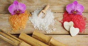 Tres pilas de sal de baño de diversos colores con el bambú y la orquídea en un fondo de madera Imágenes de archivo libres de regalías