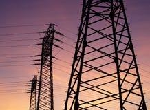 Tres pilones de la electricidad con los cables se escalonan como siluetas delante de un cielo de igualación coloreado La luna se  imagenes de archivo