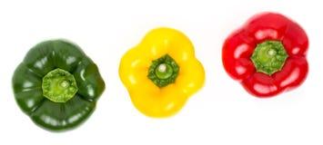 Tres pimientas de diversos colores mienten en fila en un backgr blanco Imagen de archivo