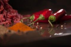 Tres pimientas rojas con la carne picadita, sazonada con pimienta y sazonada con los condimentos fotos de archivo libres de regalías