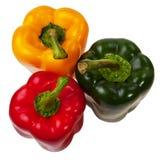 Tres pimientas rojas, verdes y amarillas. Fotos de archivo libres de regalías