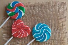 Tres piruletas coloridas del azúcar Imagen de archivo