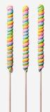 Tres piruletas largas con remolinos coloridos del arco iris Foto de archivo libre de regalías