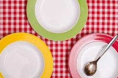 Tres placas coloreadas y una cuchara Imágenes de archivo libres de regalías