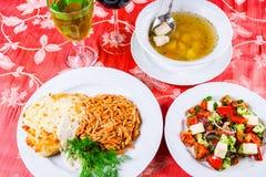 Tres placas con los platos del almuerzo en la tabla La ensalada, la sopa de los pescados y el escalope vegetales del pollo con de Imagen de archivo libre de regalías