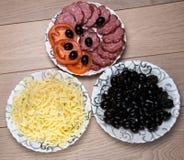 Tres placas de la salchicha, del queso rallado, del tomate y de aceitunas en la tabla de madera Foto de archivo libre de regalías