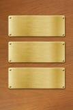 Tres placas de metal de oro sobre el fondo de madera de la textura Imagen de archivo libre de regalías