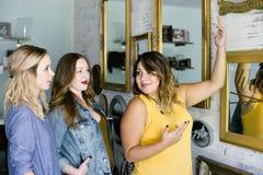 Tres planificadores de eventos de sexo femenino milenarios jovenes discuten en una reunión fotografía de archivo