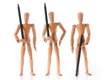 Tres plumas de tenencia de madera de los maniquíes como guardias armados Foto de archivo libre de regalías
