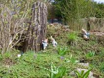 Tres pocos gnomos del jardín alrededor de un tronco de árbol Imagen de archivo