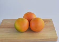 Tres pomelos, aislados en el escritorio Fotografía de archivo
