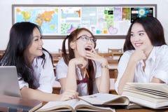 Tres principiantes que estudian y que ríen en la clase Fotos de archivo