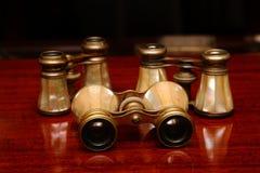 Tres prismáticos en un escritorio marrón Fotos de archivo