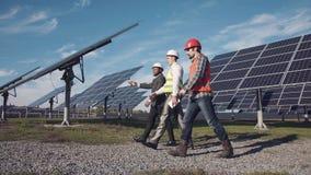 Tres profesionales en la estación de la energía solar Foto de archivo