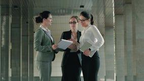 Tres profesionales hermosos que discuten su día laborable y resultados de la reunión almacen de video