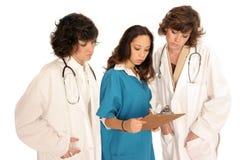 Tres profesionales médicos de las mujeres que miran sobre informe Imagen de archivo
