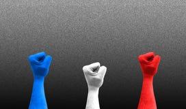 Tres pu?os en el aire con los colores de la bandera de Francia imagen de archivo