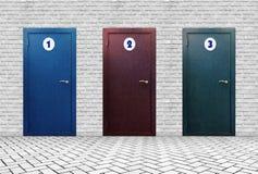 Tres puertas con diversos números en una pared de ladrillo imágenes de archivo libres de regalías