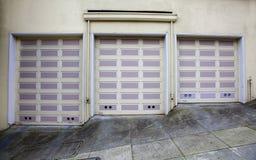 Tres puertas lavendar del garage imagen de archivo