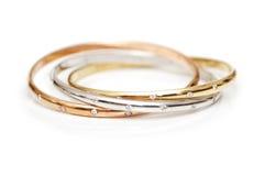 Tres pulseras del oro aisladas Fotografía de archivo